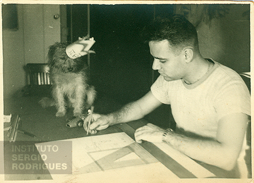 Sergio Rodrigues at age 20, making a technical drawing next to his dog Pipoca, at Castelinho, at Praia do Flamengo, No. 72 - Rio de Janeiro, in 1947.