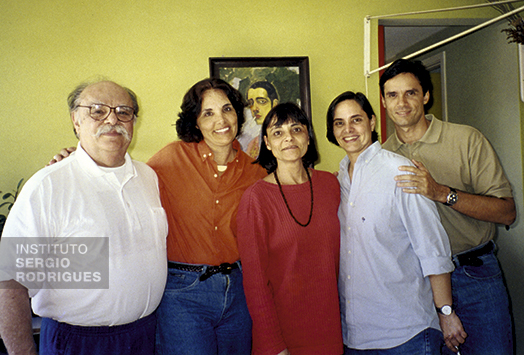 From left to right, Sergio Rodrigues next to his kids Ângela, Verônica, Adriana, and Roberto, at his home, in Rio de Janeiro, in the 2000s. In the background, self-portrait of Roberto Rodrigues, Sergio's father.